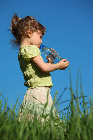 girl standing in grass drinks water from plastic bottle photo