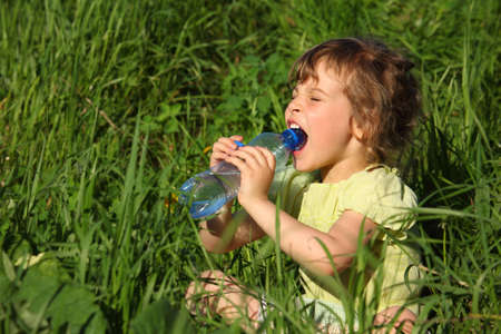 girl sits in grass and drinks water from plastic bottle photo