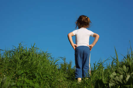 Little girl makes gymnastic in grass, rear view photo