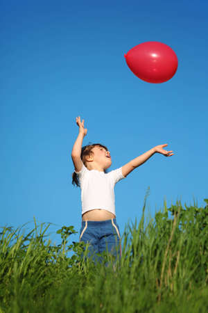 little girl plays with red balloon in grass photo
