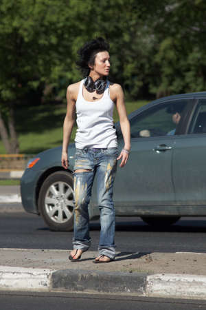 girl with ear-phones stands on road among cars photo
