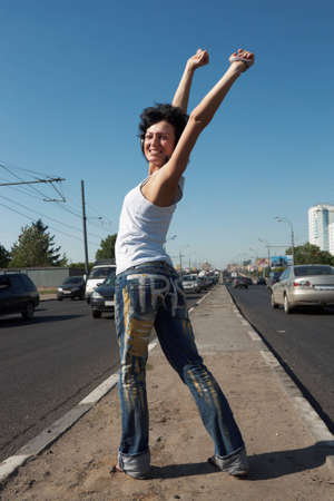 girl with lifted hands stands in half-turn on middle of road among cars photo