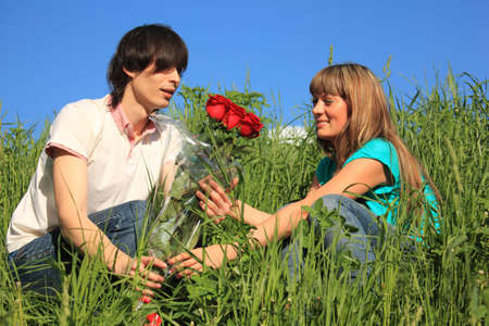 guy gives to girl bouquet of roses among grass photo