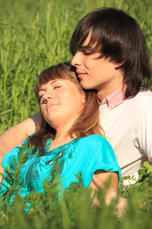 girl lies on guy sitting in grass photo