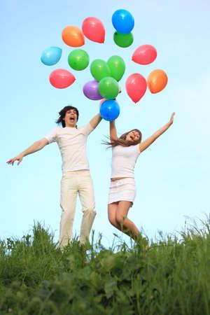 girl and  guy start multi-coloured balloons in sky