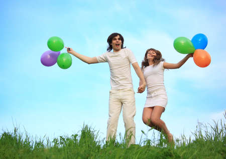 girl and guy stand in grass with multicoloured balloons in hands against sky photo