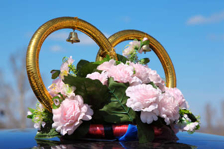 Wedding rings with bouquet on car roof photo