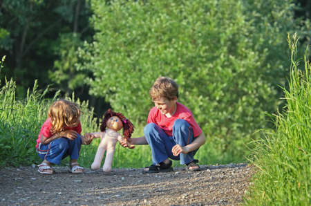poppet: Children with doll on path in park