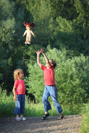 poppet: boy and girl in park toss up upward  doll, focus on doll