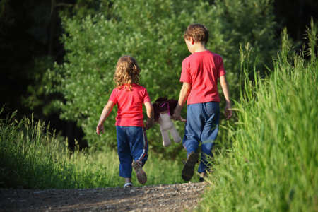 poppet: boy and girl go for a walk with doll in park, rear view Stock Photo