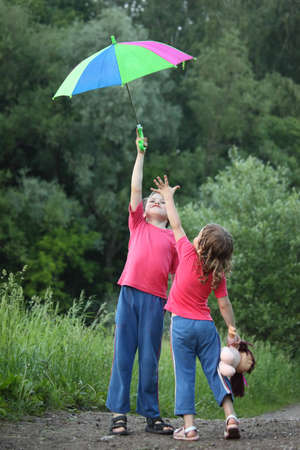 In park boy holds umbrella over head,  girl pulls to it hand photo