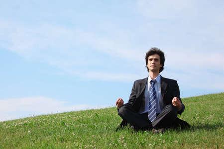 businessman meditates sitting on meadow photo