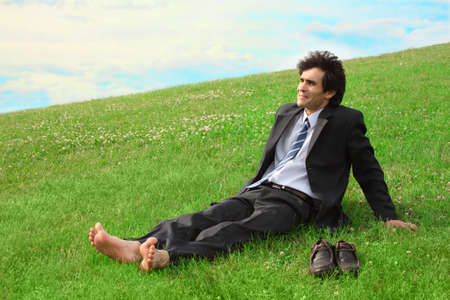 Businessman sitting on the meadow barefoot photo