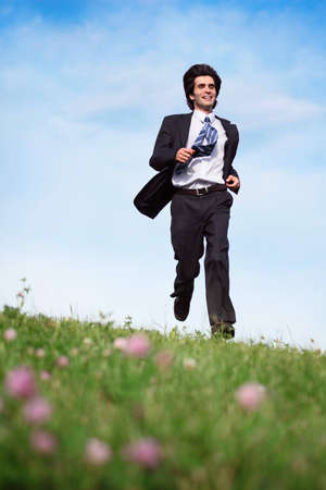 Businessman in suit running on the meadow photo