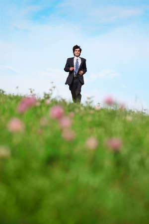 Businessman walking on the meadow photo