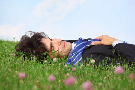 businessman lies on back on grass with closed eyes photo