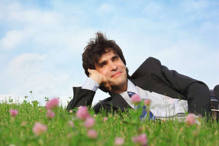 businessman lies on grass on one side with closed eyes photo