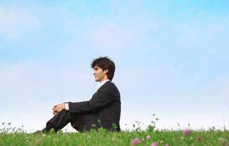 businessman sits on grass, view in profile photo