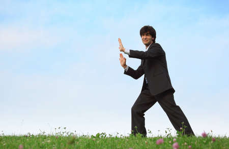 businessman pushes standing on grass photo