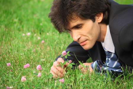 businessman lying on grass looks at clover flower photo