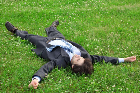 businessman lies on back on grass, having stretched legs and hands photo