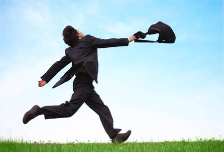 Businessman running on the meadow with bag photo