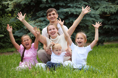 rejoice: family of five rejoice outdoor in summer sit on grass, hands up Stock Photo