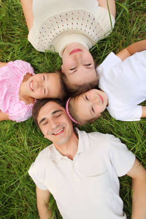 Parents with children lying on grass, view from top, head to head Stock Photo - 7837920