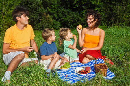 happy family of four on picnic in garden photo