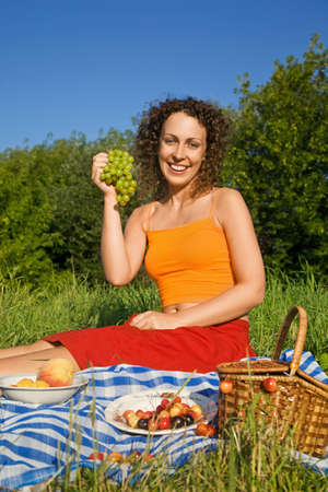 Young Women keeps in hand grape on picnic photo