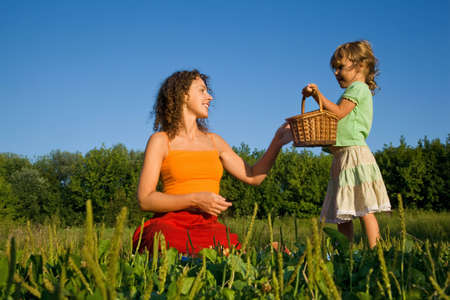pretty Little Girl gives Young Women a basket on glade photo