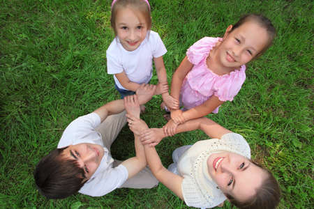 Parents with children stand having joined hands crosswise,  top view photo