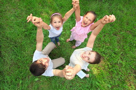 Parents with children stand having joined hands and having lifted them, top view photo