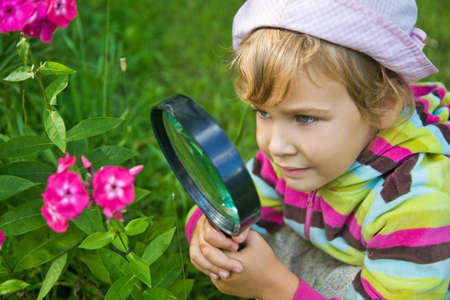 botanic: pretty Little Girl with magnifying glass looks at flower