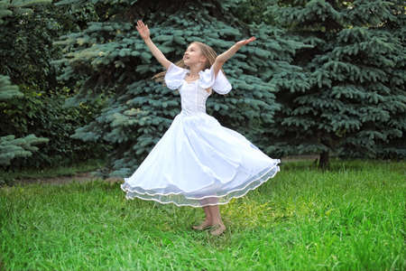 lifted hands: girl in white dress dances on lawn with lifted hands