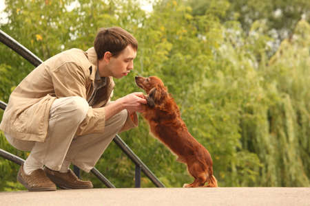 Young man plays with his adorable dachshund  outdoor photo