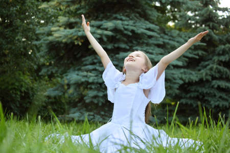 girl in white dress sits on lawn with lifted hands Stock Photo - 7837250
