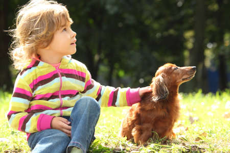 little girl with dachshund sits on grass photo