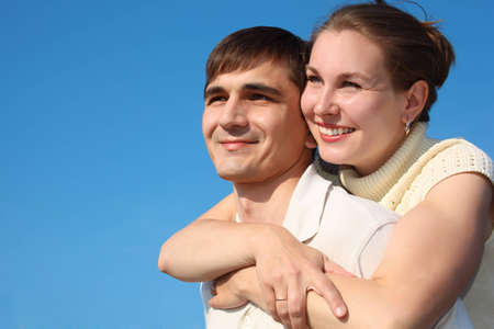 woman embraces  man from behind on sky photo