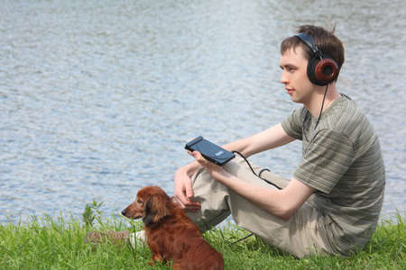 Young man liistens music in headphones sits on grass with his dachshund ashore photo
