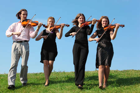 Four musicians go and playing violins against sky, front view Stock Photo - 7838054