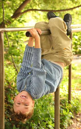 boy hangs on bars headfirst photo