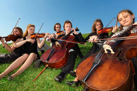 Six violinists sit on  grass and play Stock Photo - 7838249
