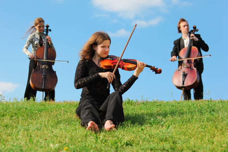 violinist and two violoncellists play on grass against sky photo