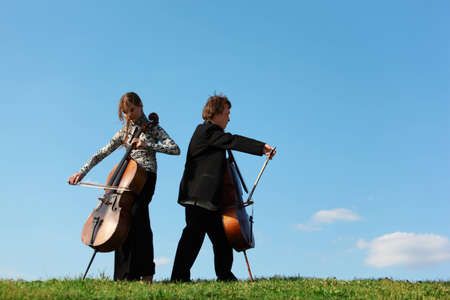 Two violoncellists play on grass against  sky photo
