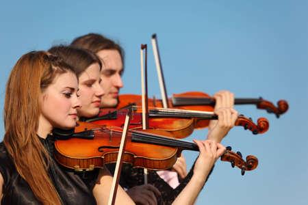 trio: trio of violinists plays against sky Stock Photo