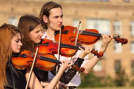 trio: trio of violinists plays outdoor Stock Photo