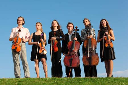 musica clasica: Seis violinistas pararse sobre hierba contra el cielo