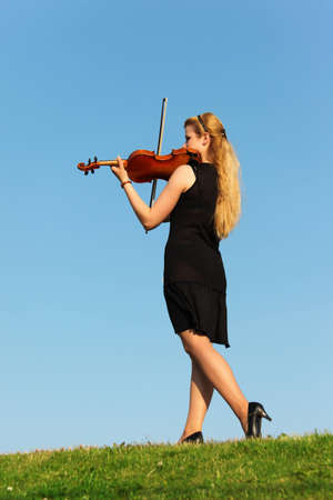 girl stands on grass and plays violin against  sky  photo