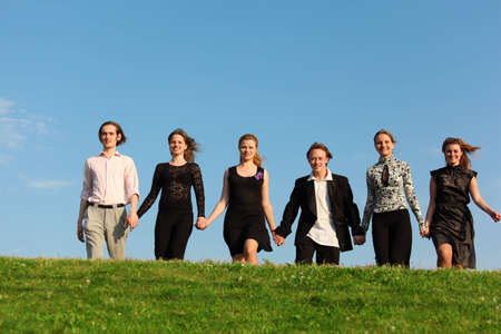joined hands: Seis amigos van en pradera habiendo se uni� a manos